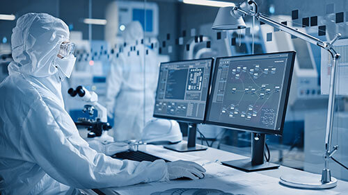 Image of lab technician monitoring particle data screens for cleanroom